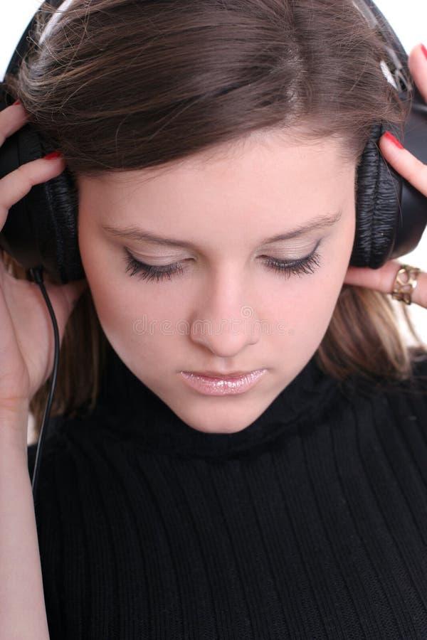 El Brunette con los auriculares Meditates imagenes de archivo