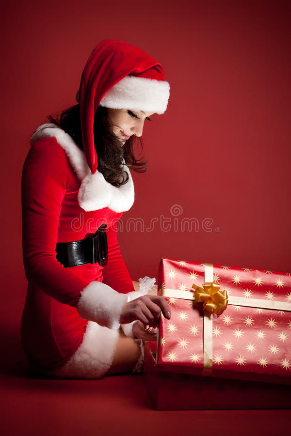 El brunette hermoso en alineada de la Navidad abre el regalo fotos de archivo