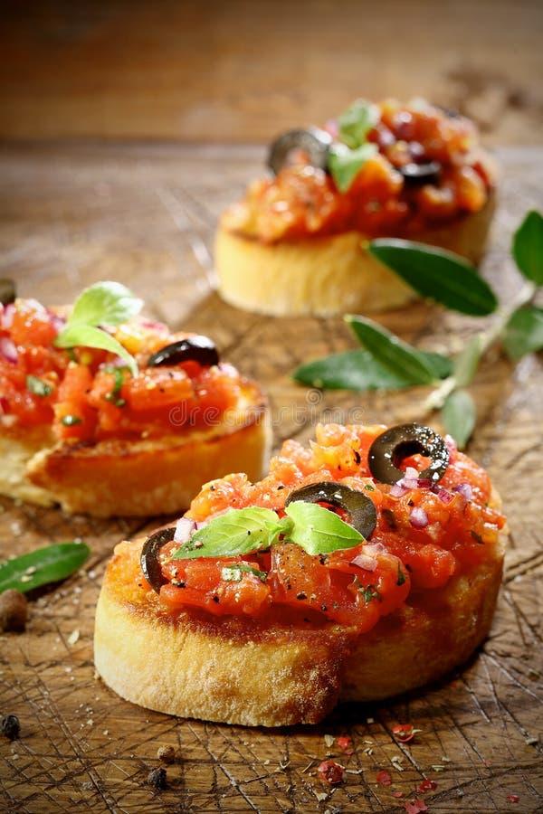 Bruschetta del tomate rematado con la aceituna y la albahaca fotos de archivo