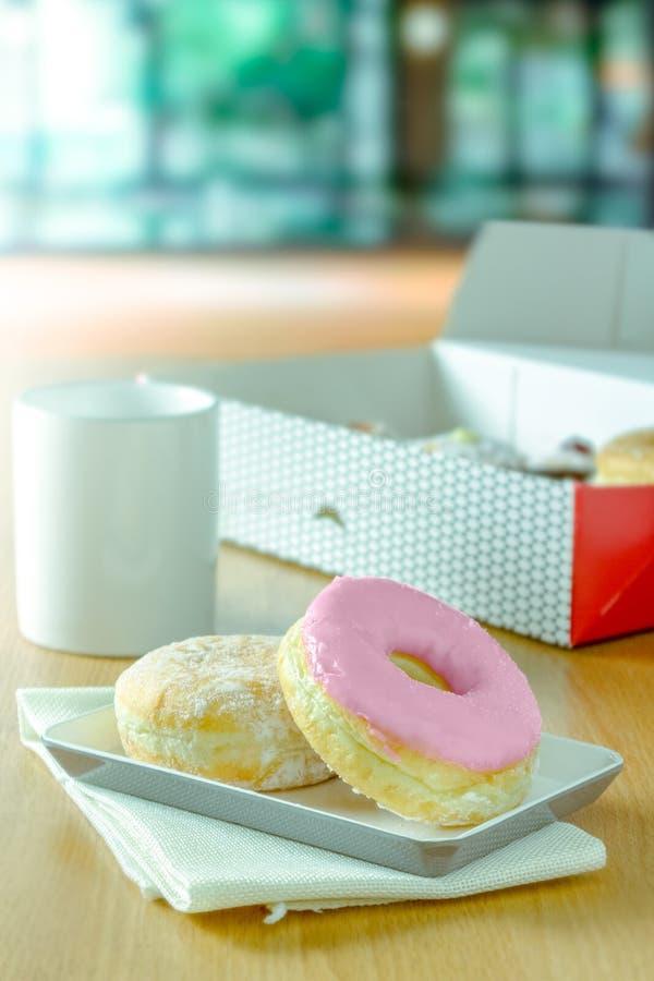El buñuelo de la fresa se pone con otro buñuelo en plato y la caja de anillos de espuma con la taza de café blanca en la tabla en foto de archivo libre de regalías