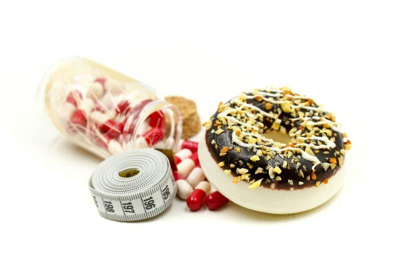 El buñuelo que ata por la cápsula de la cinta métrica y de la droga de medicina, dietética para el concepto delgado de la forma,  foto de archivo libre de regalías
