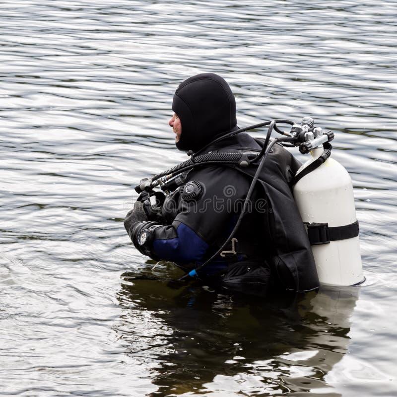 El buceador entra en el agua del lago de la montaña técnicas practicantes para los salvadores de la emergencia inmersión en agua  foto de archivo
