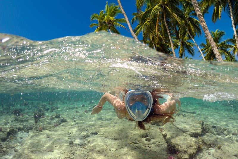 El bucear cerca de una isla tropical Nadadas hermosas de la muchacha en el agua fotos de archivo libres de regalías