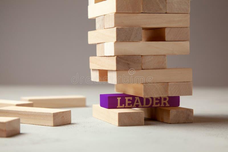 El buen líder está construyendo el equipo y a la compañía acertados en negocio Torre de bloques de madera con el líder de la insc foto de archivo libre de regalías