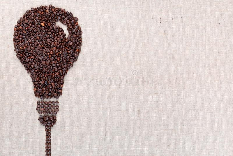El bulbo el?ctrico hecho de los granos de caf? al rev?s en la textura del linea, alineada se fue fotos de archivo