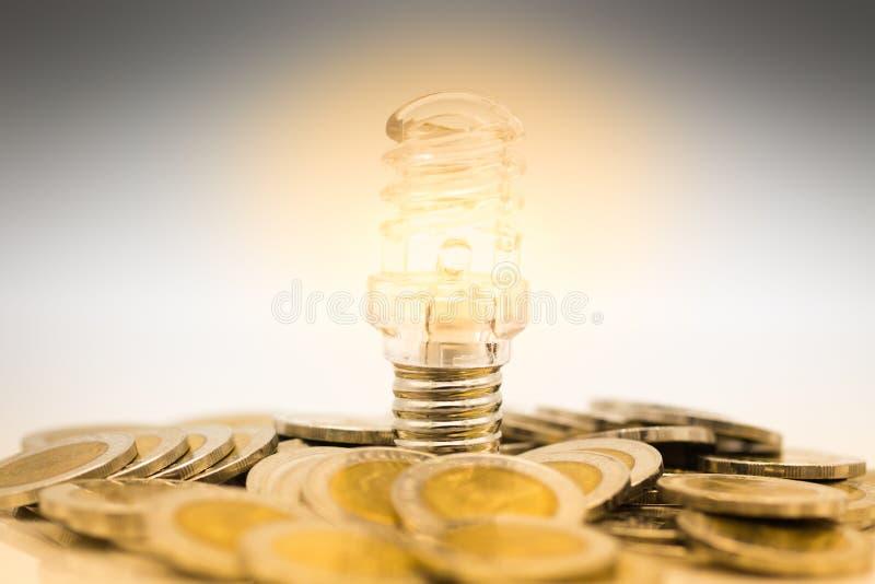 El bulbo es pila colocada de monedas, el bulbo se enciende en oscuridad Uso de la imagen para encontrar una salida en la oscurida foto de archivo libre de regalías