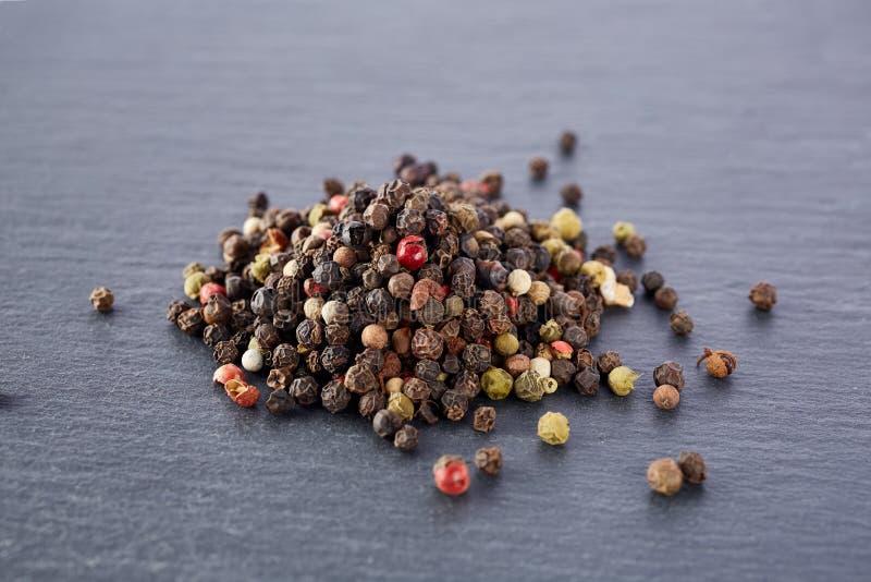 El bulto de diversas semillas de los granos de pimienta de la pimienta se mezcla en piedra oscura fotografía de archivo libre de regalías