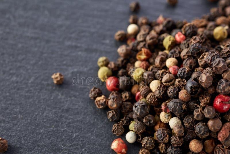 El bulto de diversas semillas de los granos de pimienta de la pimienta se mezcla en piedra oscura foto de archivo