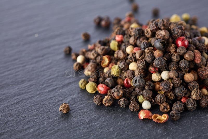 El bulto de diversas semillas de los granos de pimienta de la pimienta se mezcla en piedra oscura imágenes de archivo libres de regalías