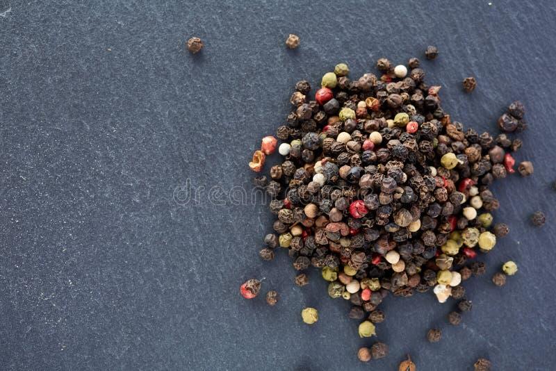 El bulto de diversas semillas de los granos de pimienta de la pimienta se mezcla en piedra oscura imagenes de archivo