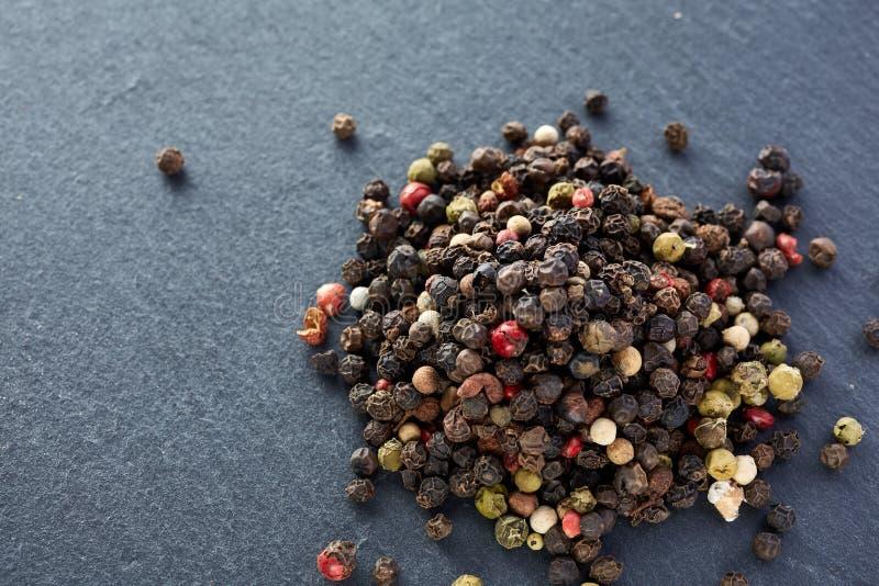 El bulto de diversas semillas de los granos de pimienta de la pimienta se mezcla en piedra oscura imagen de archivo libre de regalías