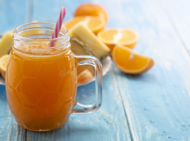 El buque de cristal con el jugo de la naranja con una paja en una tabla azul imagen de archivo