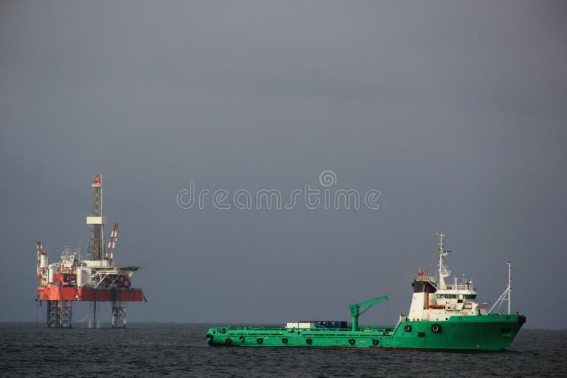 El buque de la fuente está en ancladero, con la plataforma de perforación en el fondo fotografía de archivo libre de regalías