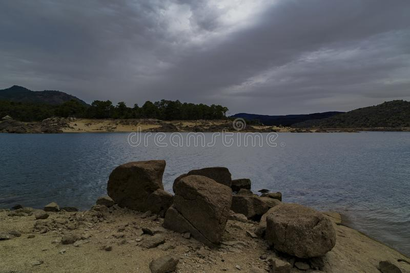El Burguillo reservoir. Water, trees and rocks. stock photography