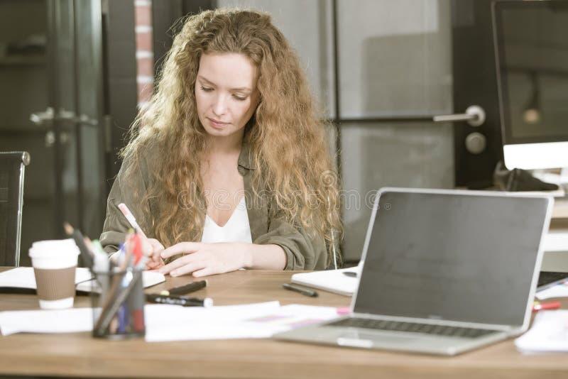 El businesswomanWorking joven hermoso en su escritorio con el café MU imágenes de archivo libres de regalías