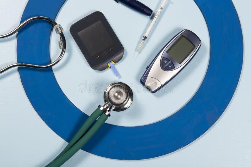 El círculo azul con un poco de equipo de la diabetes hace el tratamiento la enfermedad foto de archivo