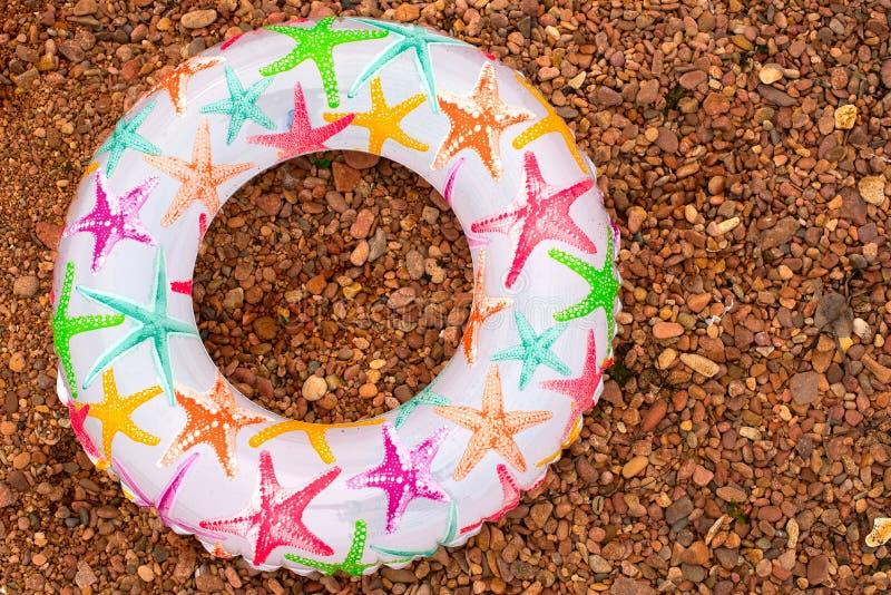 El círculo inflable colorido del bebé miente en la orilla imágenes de archivo libres de regalías