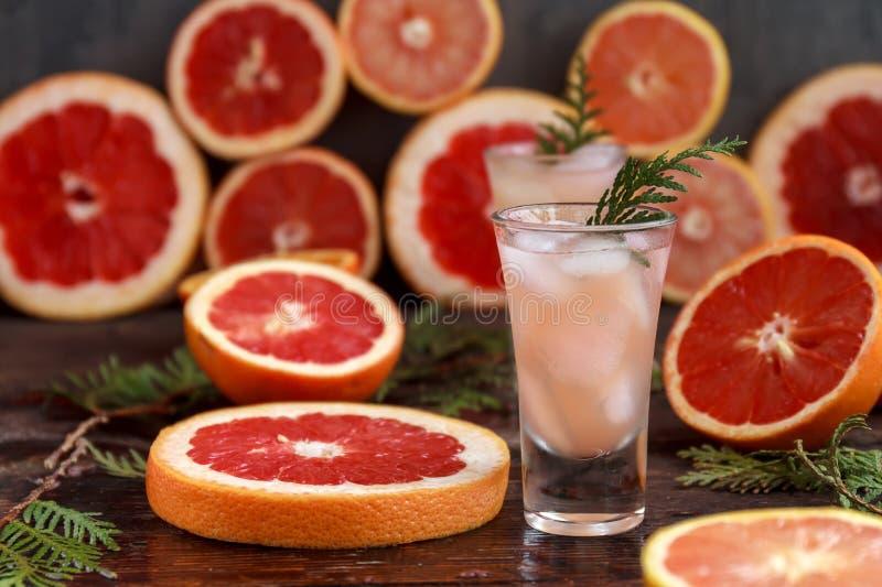 El cóctel alcohólico fresco con el pomelo y fruta cítrica, hielo y jugo, bebe el vidrio en un tablero de madera, viejo estilo  foto de archivo libre de regalías