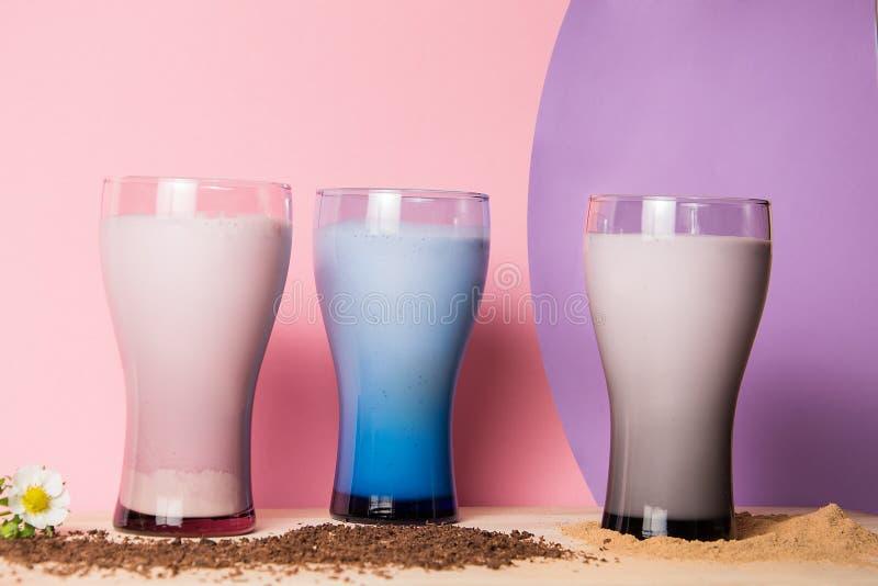 El cóctel apetitoso de la leche tres sirvió en vidrios en la placa de madera y coloreó el fondo foto de archivo libre de regalías