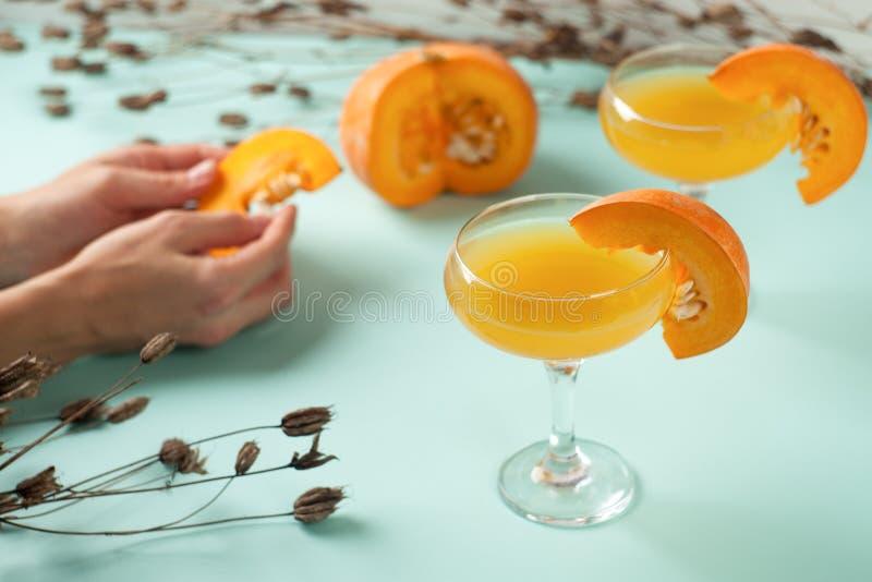 El cóctel de Halloween, bebida anaranjada de la calabaza con las especias en vidrios adornó la rebanada de la calabaza fotos de archivo libres de regalías