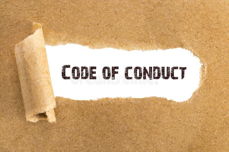 El código de conducta del texto que aparece detrás del papel marrón rasgado fotografía de archivo