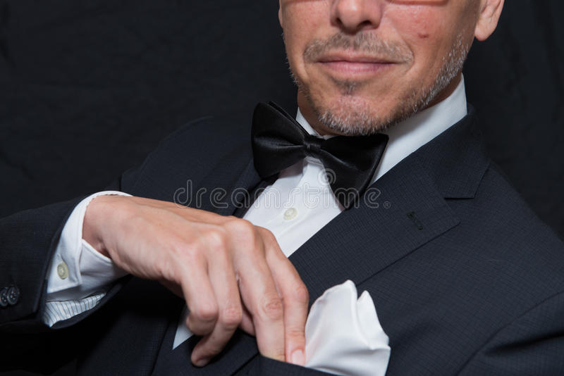 El caballero en lazo negro fija el cuadrado del bolsillo, horizontal fotografía de archivo libre de regalías
