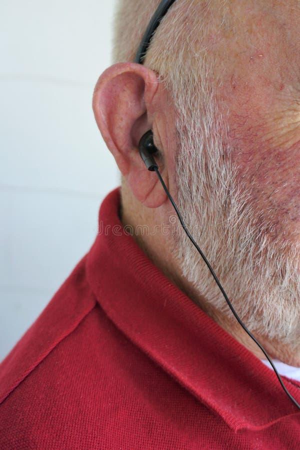 El caballero envejecido escucha con auriculares de botón foto de archivo libre de regalías