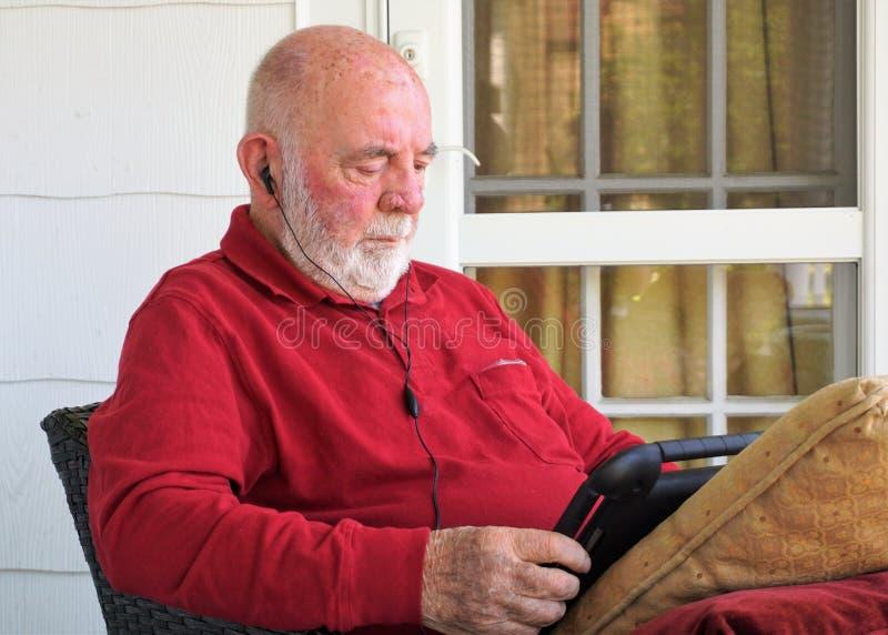 El caballero envejecido escucha con auriculares de botón y lee el dispositivo imagen de archivo libre de regalías