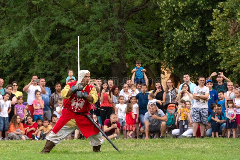 El caballero medieval en el traje rojo con una espada muestra habilidades caballerescas encendido en el festival internacional de imagen de archivo libre de regalías