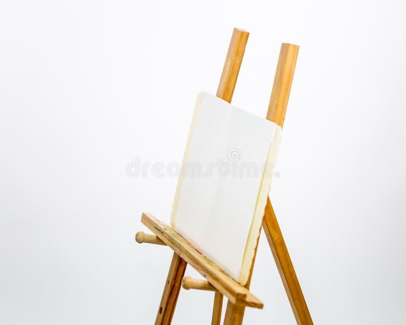 El caballete del artista para pintar en el fondo blanco imagen de archivo