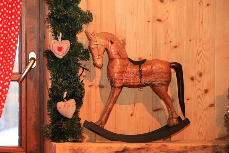 El caballo mecedora de madera decorativo de la decoración de la Navidad y del Año Nuevo juega en estilo retro foto de archivo