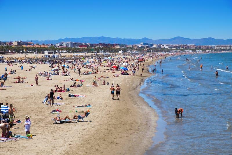 El Cabanyal and La Malvarrosa beaches in Valencia, Spain. VALENCIA, SPAIN - JUNE 22: Sunbathers at El Cabanyal and La Malvarrosa beaches on June 22, 2016 in royalty free stock images