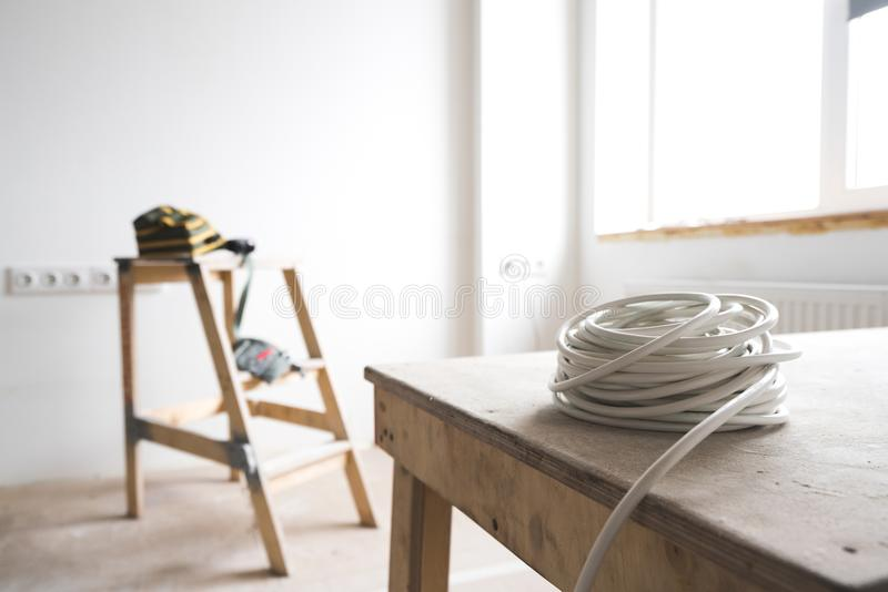 El cable eléctrico blanco descansa sobre la escalera de la cabra dentro del apartamento y de la reparación fotos de archivo