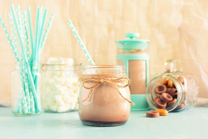 El cacao caliente se vierte en el tarro En el pote del café del fondo, melcochas y dulces del chocolate El fondo en foto de archivo libre de regalías
