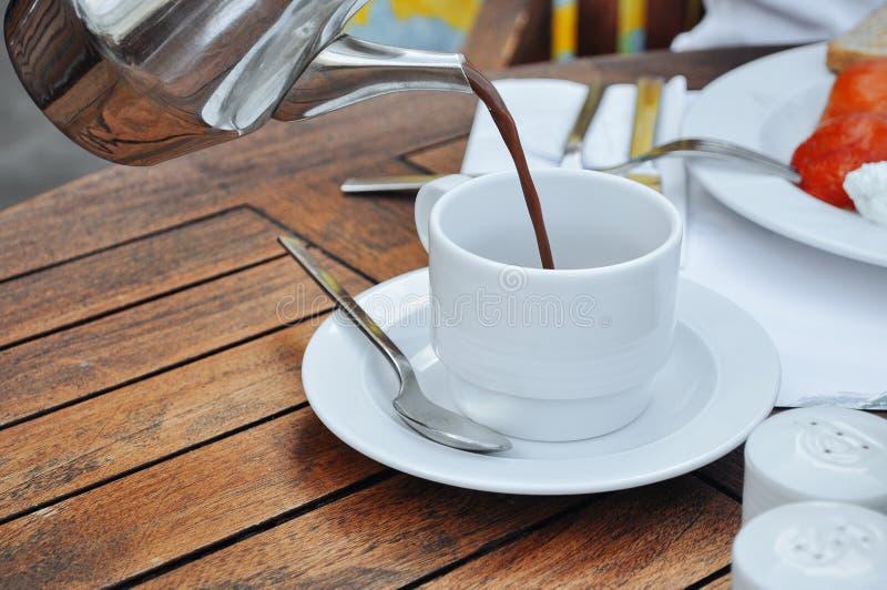 El cacao vertió en la taza blanca foto de archivo