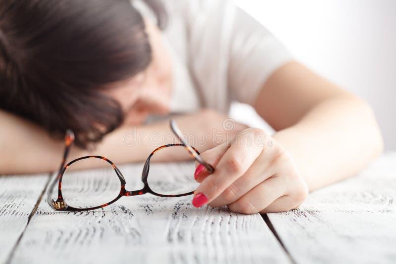 El caer cansada de la empresaria dormido en su lugar de trabajo con el gl de los ojos foto de archivo
