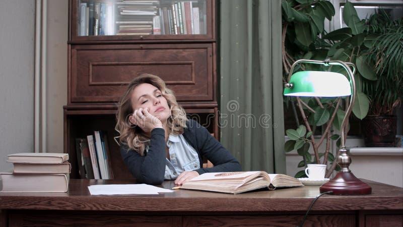 El caer cansada de la mujer joven dormido sobre un libro mientras que se sienta en la tabla foto de archivo