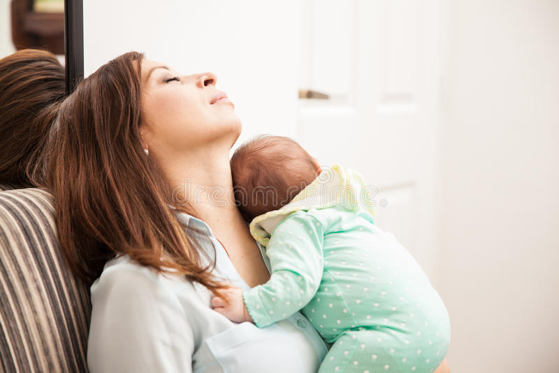 El caer de la mamá dormido con su bebé imagen de archivo