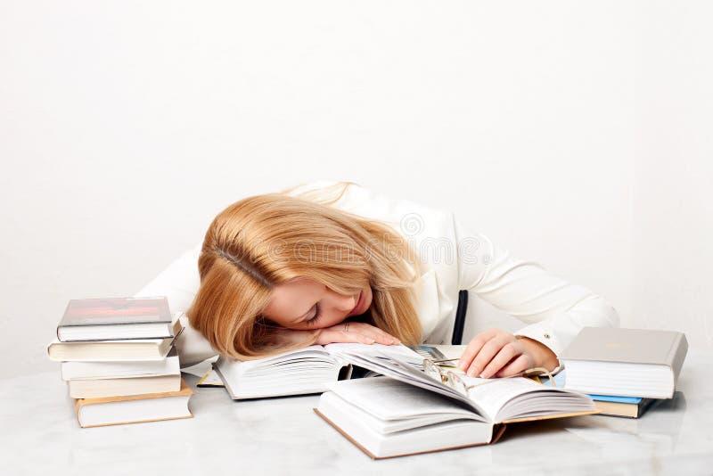El caer de la mujer joven dormido mientras que estudia imagen de archivo libre de regalías