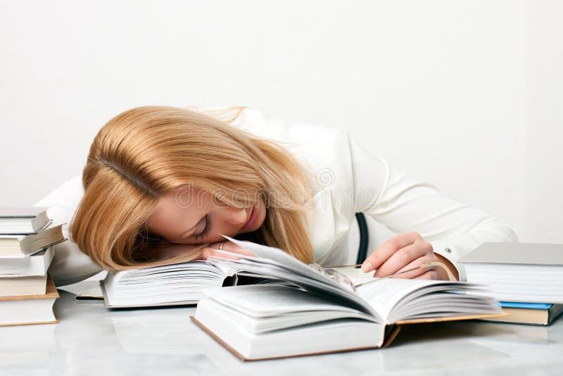 El caer de la mujer joven dormido mientras que estudia foto de archivo libre de regalías