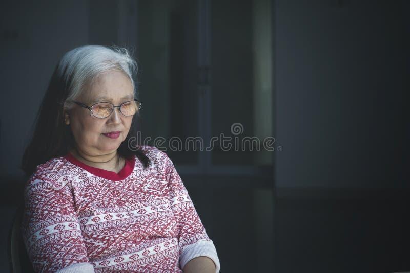 El caer de la mujer mayor dormido en la silla de ruedas imagenes de archivo