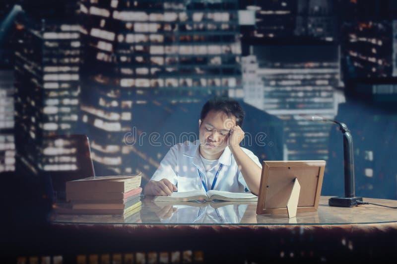 El caer del estudiante dormido mientras que estudia en un escritorio Sitio de la oficina tirado detrás del vidrio fotos de archivo libres de regalías