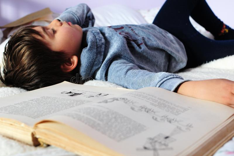El caer del muchacho dormido mientras que lee imagen de archivo
