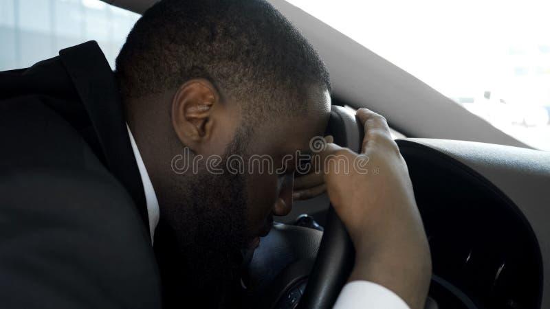 El caer personal con exceso de trabajo del conductor dormido en el volante del coche, hombre cansado imagen de archivo libre de regalías
