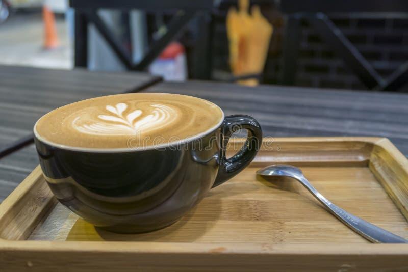 El café caliente del Latte del arte en una taza en la bandeja de madera y la cafetería empañan el fondo con imagen del bokeh fotos de archivo
