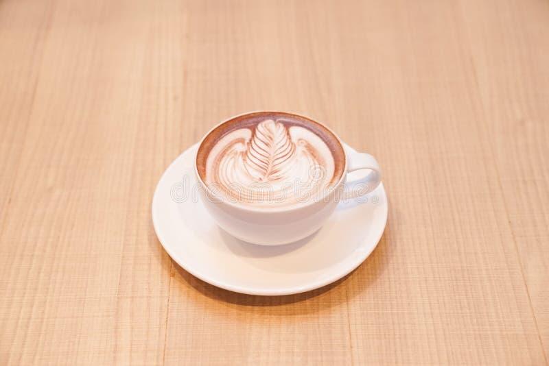 El café caliente del latte lindo de la hoja en la taza blanca en la tabla de madera, leyó para servir fotos de archivo libres de regalías