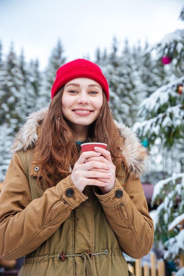 El café de consumición de la mujer cerca adornó el árbol de navidad en bosque del invierno imagenes de archivo