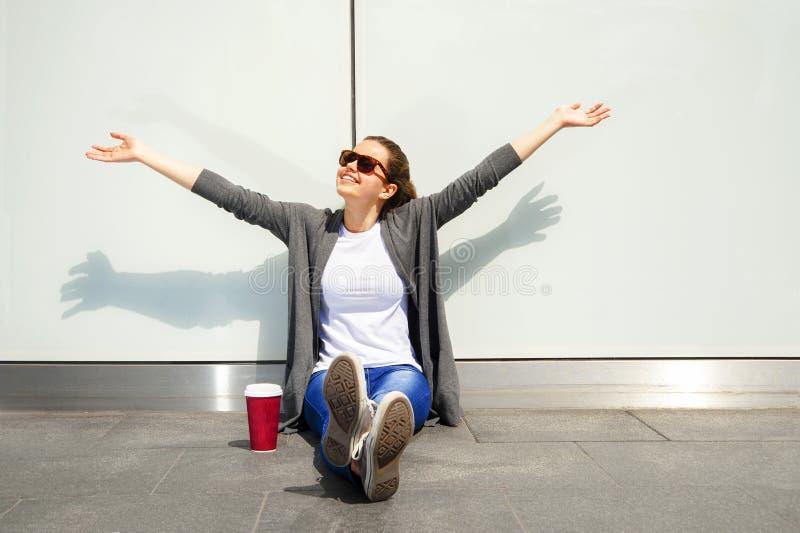 El café de consumición de la mujer por la mañana en la calle se relaja sobre la pared blanca imagen de archivo libre de regalías