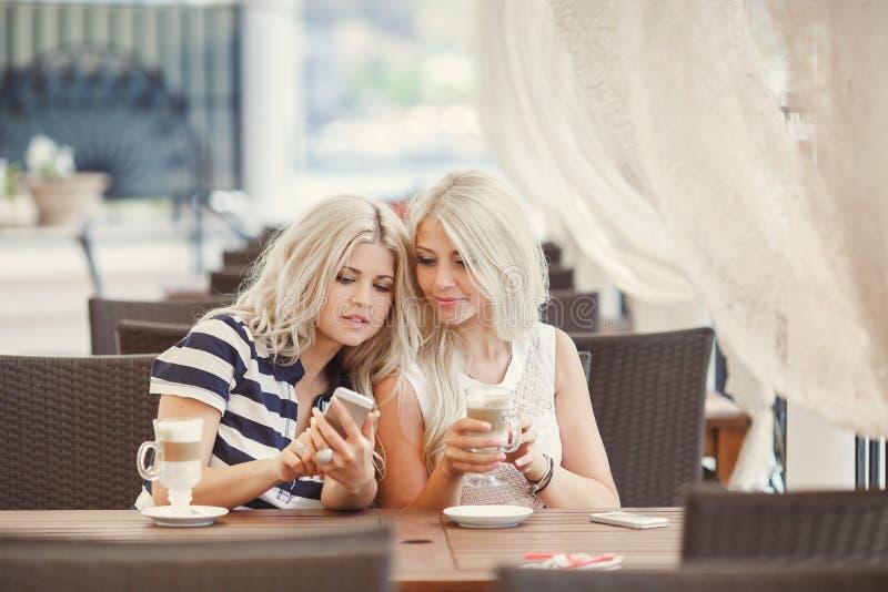 El café de la bebida de dos muchachas y utiliza el teléfono fotos de archivo