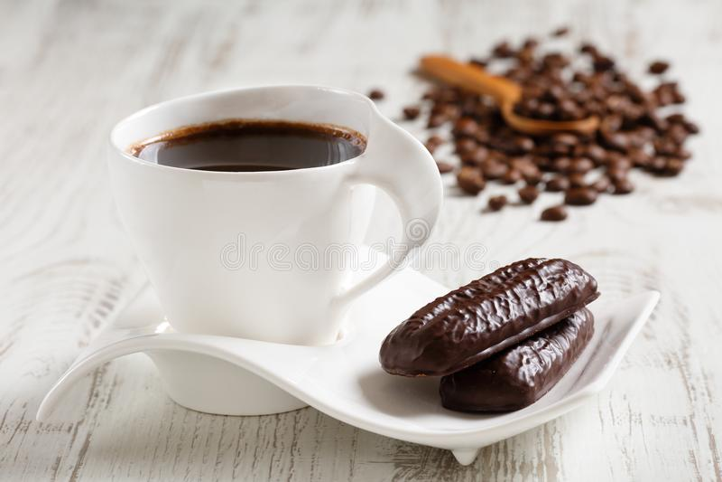 El café de la mañana en la taza de cerámica blanca con la onda formó el platillo y dos galletas del cacao en la tabla rústica de  imagen de archivo